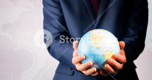 Close up of travel agent holding globe against white map