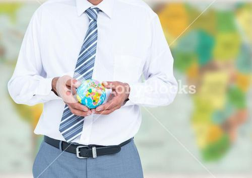 Travel agent mid section holding globe against blurry map