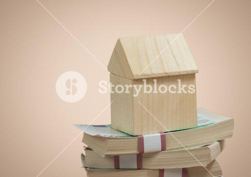 Wooden house sitting on money pile notes against beige background