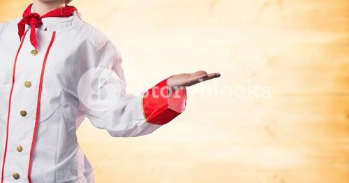 Chef with hand out at side against blurry yellow wood panel