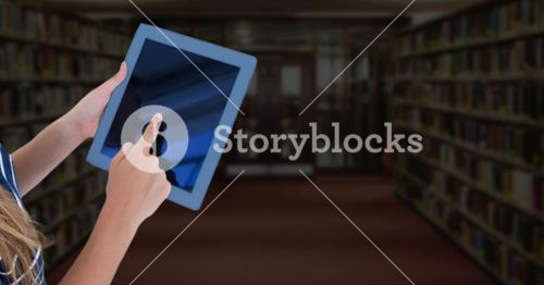 Womans hands touching tablet in Library