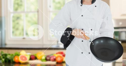 Chef with wok against blurry kitchen with vegetables