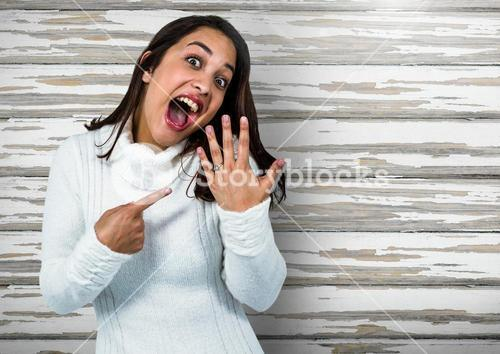 Engaged Woman with ring excited against wood