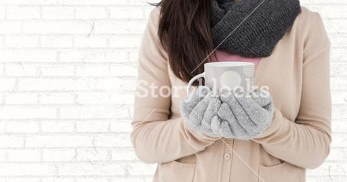 Woman mid section with polka dot mug against white brick wall