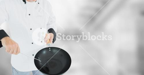 Chef with wok against blurry grey room
