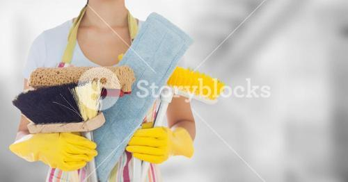 Woman in apron with brushes against blurry grey room