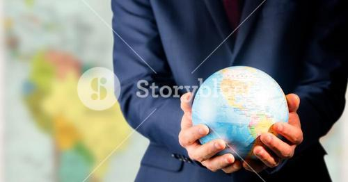 Close up of travel agent holding globe against blurry map