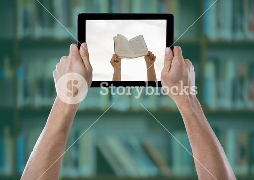 Hand with tablet showing hands with book against blurry bookshelf with green overlay