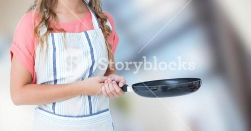 Woman in apron with frying pan against blurry window