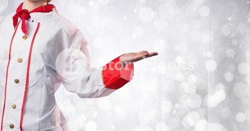 Chef with hand out at side against white bokeh