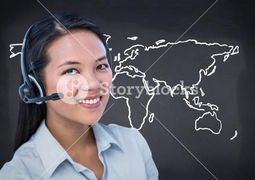 Travel agent with headset against white map and navy chalkboard