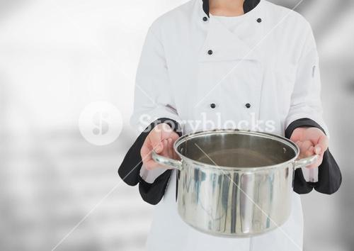 Chef with saucepan against blurry grey stairs
