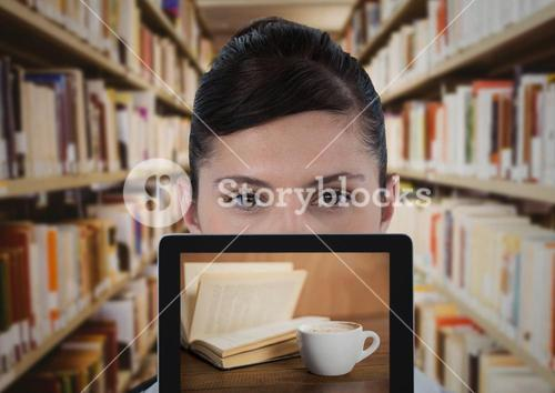 Woman with tablet showing book and coffee against blurry bookshelves