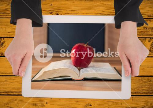 Hands with tablet on yellow table showing book with red apple