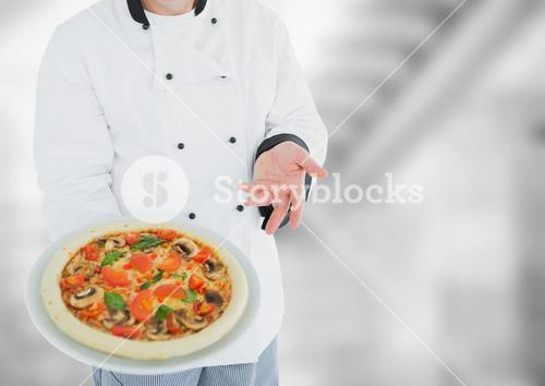 Chef with pizza against blurry grey stairs