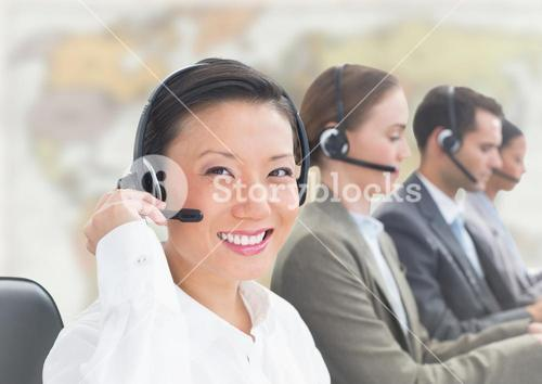 Travel agents with headsets against blurry map