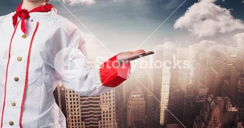 Chef with hand out at side against blurry skyline