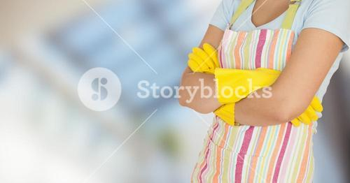 Woman in apron with arms folded against blurry window