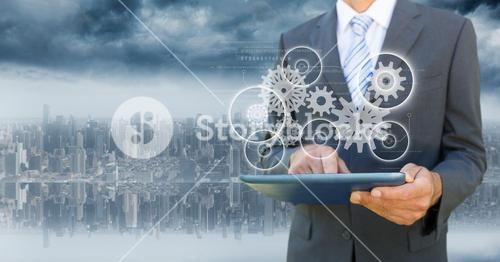 Business man  with tablet and white gear graphic with flare against blurry skyline