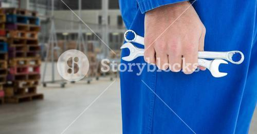 Mechanic legs and tools in hand against blurry warehouse