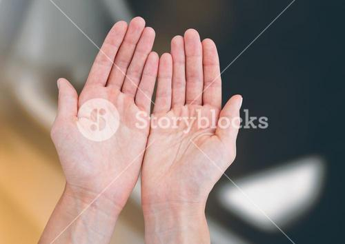 Hands open together reaching against blurred background