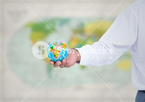 Arm with globe against blurry map