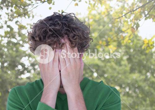 Upset stressed man hiding in hands under trees