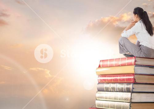 Businesswoman sitting on Books stacked by sun clouds