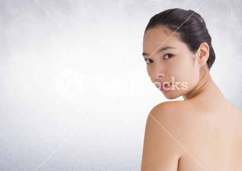 Woman looking over shoulder against white wall