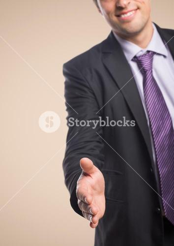 Business man with hand outstretched against cream background