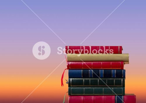 Books stacked by twilight sky