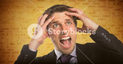 Business man hands on head against yellow brick wall