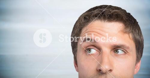 Top of man's head against blurry grey wood panel