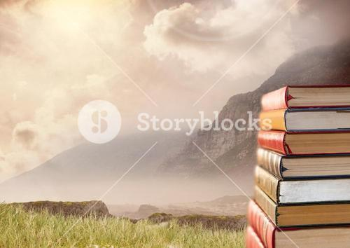 Books stacked by mountain sky