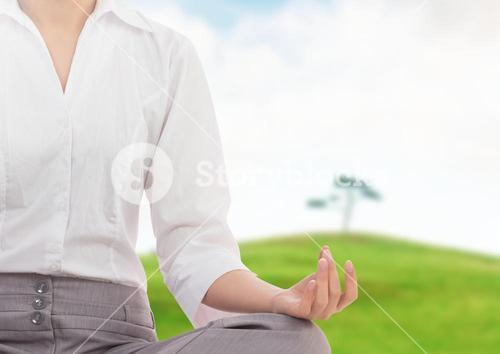 Woman Meditating by green hill and tree