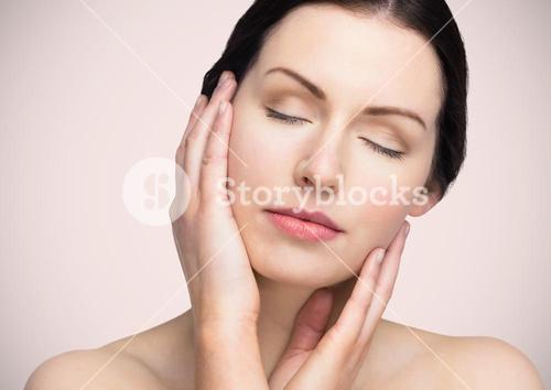 Woman with hands on face against pink background
