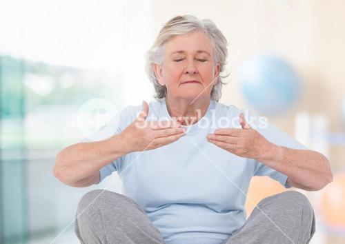 Old woman Meditating against bright background