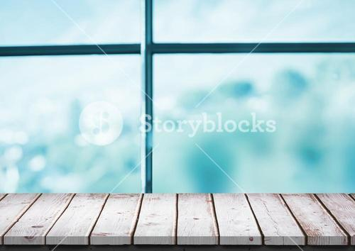 White wood table against blurry blue window