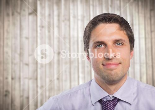 Close up of man in lavendar shirt against blurry wood panel