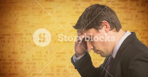 Portrait of business man hand on forehead against yellow brick wall