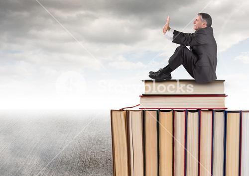 Man sitting on Books stacked by grey cloudy sky