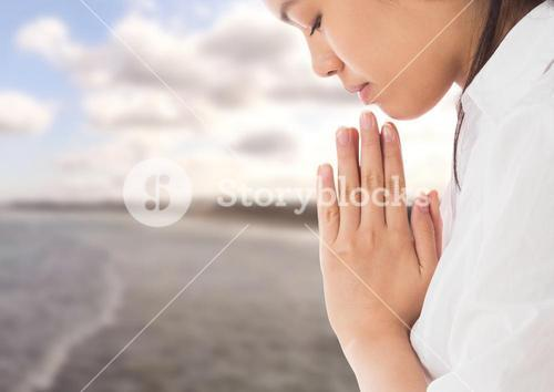 Woman praying Yoga Meditating by sea