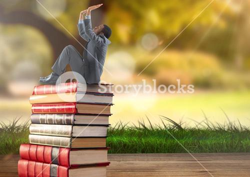 Businessman sitting on Books stacked by greenery nature