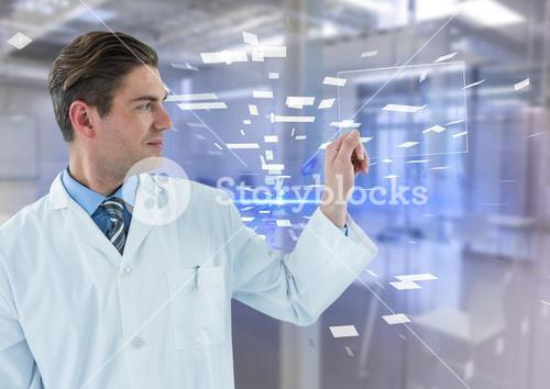 Man in lab coat holding up glass device against blue interface and blurry lab