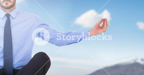 Businessman Meditating by sky mountain