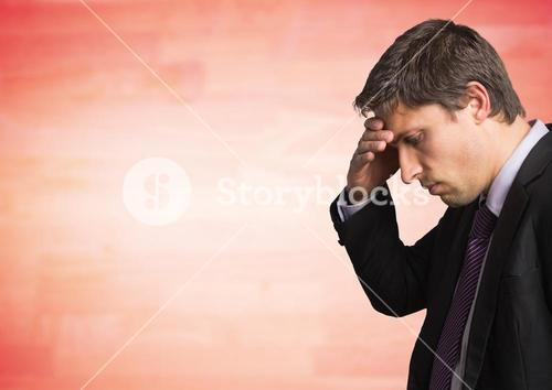 Business man portrait with hand on forehead against blurry red wood panel