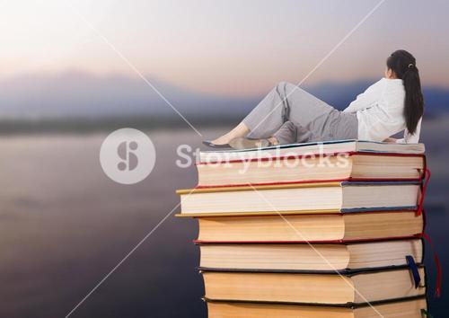 Businesswoman lying on Books stacked by sea lake