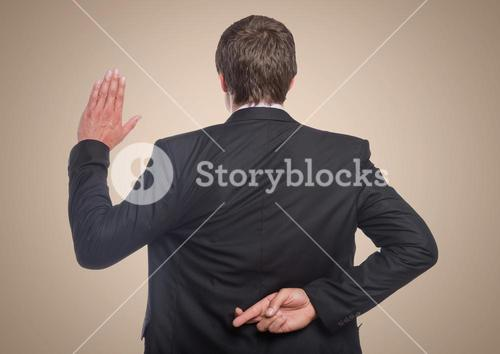 Back of business man with hand up and fingers crossed against cream background