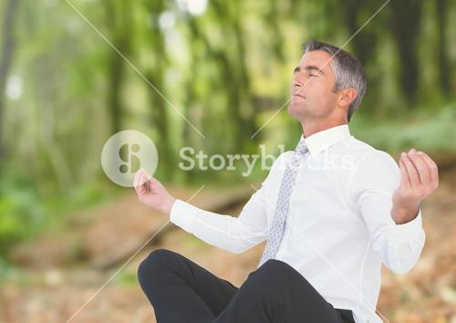 Businessman Meditating by forest