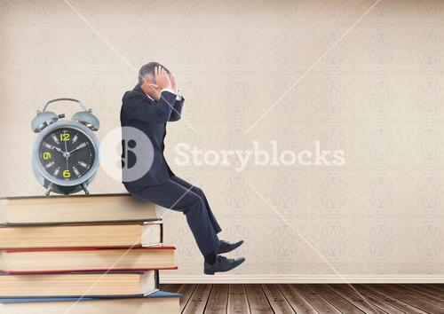 Stressed businessman sitting on Books stacked on shelf with clock